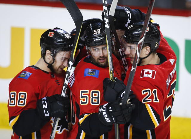 Calgary Flames' Oliver Kylington, centre, of Sweden, celebrates his goal with teammates Andrew Mangiapane, left, and Garnet Hathaway during first period NHL hockey action against the Carolina Hurricanes, in Calgary, Tuesday, Jan. 22, 2019. (Jeff McIntosh/The Canadian Press via AP)