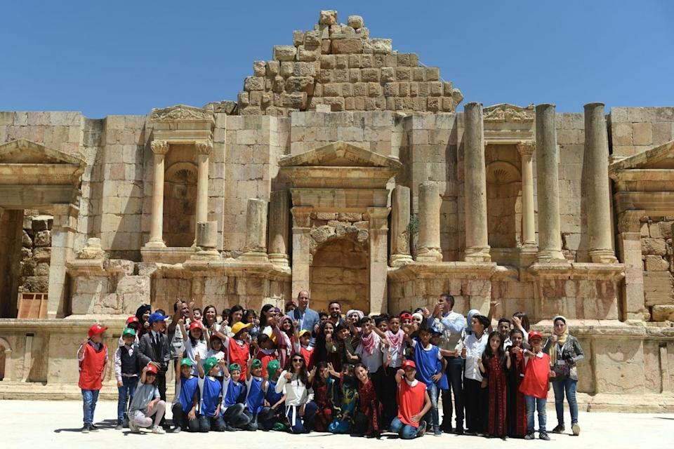 Jerash: William and the Crown Prince pose with local schoolchildren at the spot (PA)