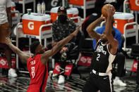 Los Angeles Clippers forward Kawhi Leonard, right, shoots as Houston Rockets forward Jae'Sean Tate defends during the first half of an NBA basketball game Friday, April 9, 2021, in Los Angeles. (AP Photo/Mark J. Terrill)