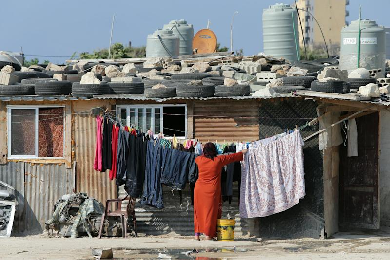 A Syrian refugee woman hangs up laundry in a make-shift camp in a poor neighbourhood of the Lebanese coastal city of Tripoli, north of Beirut, on May 26, 2014 (AFP Photo/Joseph Eid)
