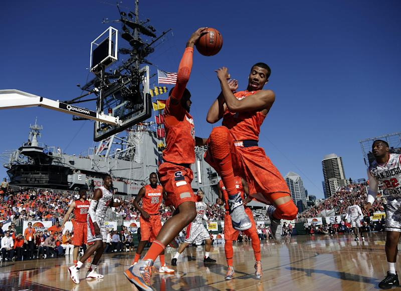Syracuse forward James Southerland, left, saves a ball from going out of bounds as Michael Carter-Williams, right, jumps out of the way while playing San Diego State during the first half of an NCAA college basketball game on the deck of the USS Midway, Sunday, Nov. 11, 2012, in San Diego. (AP Photo/Gregory Bull)