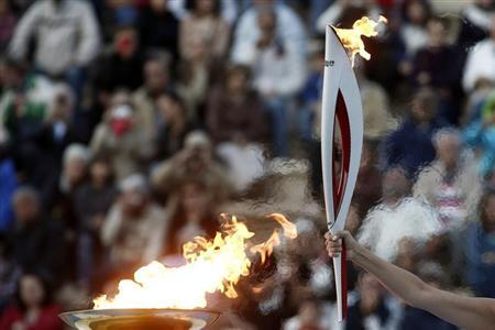 Greek actress Menegaki raises an Olympic torch of the Sochi 2014 Winter Games during a handover ceremony at the Panathenean stadium in Athens