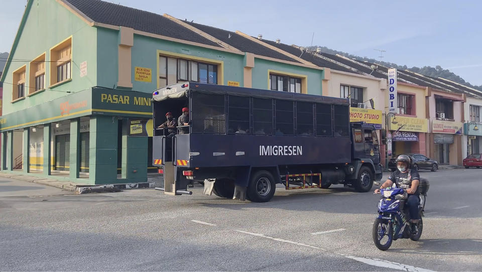In this image taken from a video, an immigration truck with security and unidentified people drives on a road that leads to Lumut Naval Base Tuesday, Feb. 23, 2021 in Lumut, Malaysia. A Malaysian court Tuesday ordered a halt to the planned deportation of 1,200 Myanmar migrants to hear an appeal by two human rights groups, which say the migrants included refugees, asylum seekers and minors. (AP Photo)