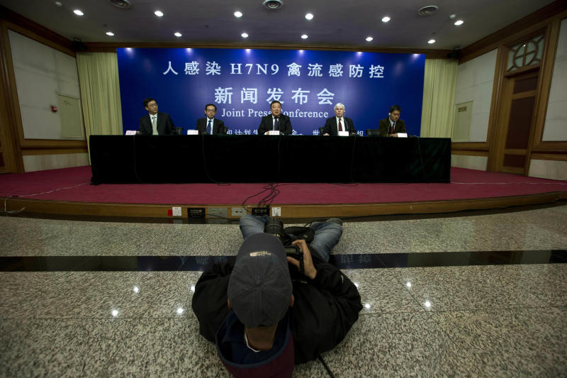 A photographer takes a photo of a joint press conference by Chinese health officials and World Health Organization representatives, from left, Deng Haihua, spokesman for China's Commission of Health and Family Planning, Feng Zhijian, head of the emergency office of China's Disease Control and Prevention Center or CDC, Liang Wannian head of a Chinese government office in charge of H7N9 bird flu prevention control, Michael O'Leary, head of the WHO's office in China, and Sirenda Vong, the WHO's Emerging Infectious Diseases expert, in Beijing, China, Monday, April 8, 2013. The World Health Organization is talking with the Chinese government about sending international experts to China to help investigate a new bird flu strain that has killed six. Most of the 21 people stricken so far got severely ill. (AP Photo/Ng Han Guan)