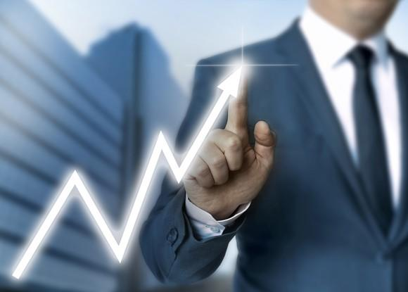 Man in suit pointing to arrow chart indicating gains