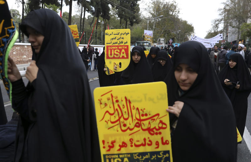 """Demonstrators hold anti-U.S. placards in Arabic reading; during an annual rally in front of the former U.S. Embassy in Tehran, Iran, Monday, Nov. 4, 2019. Reviving decades-old cries of """"Death to America,"""" Iran on Monday marked the 40th anniversary of the 1979 student takeover of the U.S. Embassy in Tehran and the 444-day hostage crisis that followed as tensions remain high over the country's collapsing nuclear deal with world powers. The Arabic in top reads: """"We shall never accept humiliation."""" (AP Photo/Vahid Salemi)"""