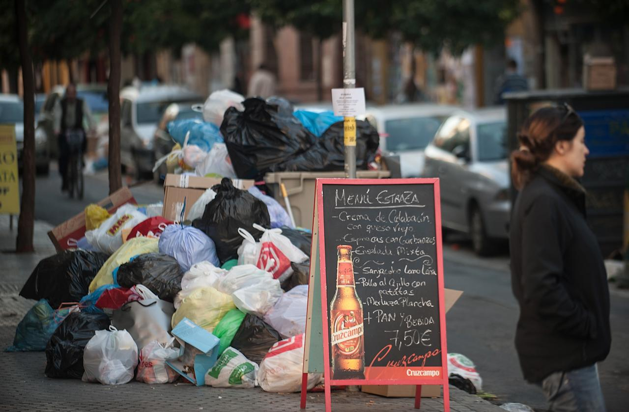 SEVILLE, SPAIN - FEBRUARY 05:  Garbage piles up on the street beside a bar sign displaying lunch prices during the ninth day of the Seville waste disposal strike on February 5, 2013 in Seville, Spain. Workers are striking over demands they take a 5% pay cut and extend their working week to 37.5 hours.  (Photo by Denis Doyle/Getty Images)