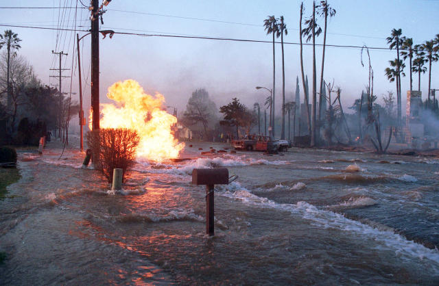 FILE - In this Jan. 17, 1994 file photo, gas from a ruptured supply line burns as water from a broken water main floods Balboa Boulevard in the Granada Hills area of Los Angeles. The fire from the gas main destroyed two homes, right. Twenty-five years ago this week, the violent, pre-dawn earthquake shook Los Angeles from its sleep, and sunrise revealed widespread devastation, with dozens killed and $25 billion in damage. (AP Photo/Lenny Ignelzi, File)