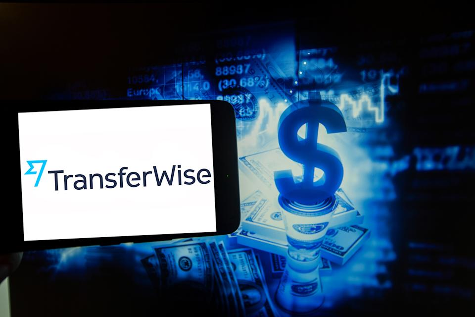 The logo of TransferWise is seen on a screen of a smartphone next to an illustration of money and stock market. (Photo illustration by Alexander Pohl/NurPhoto via Getty Images)