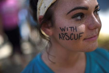 Emma Diluzio, 20, a West Chester University junior, demonstrates with university employees from the APSCUF union representing 5,500 Pennsylvania university and college employees after failing to reach a contract deal with the state education system in West Chester, Pennsylvania, U.S., October 19, 2016. REUTERS/Mark Makela