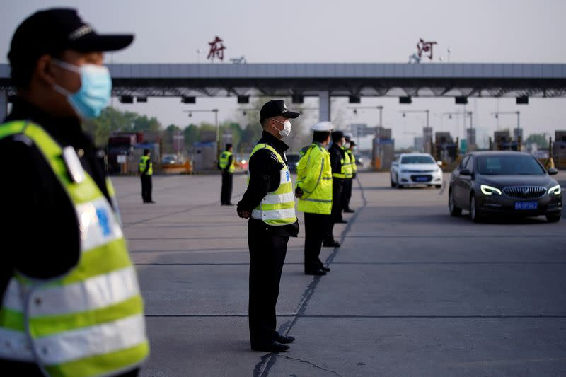 Police officers stand guard at a toll station of an expressway in Wuhan