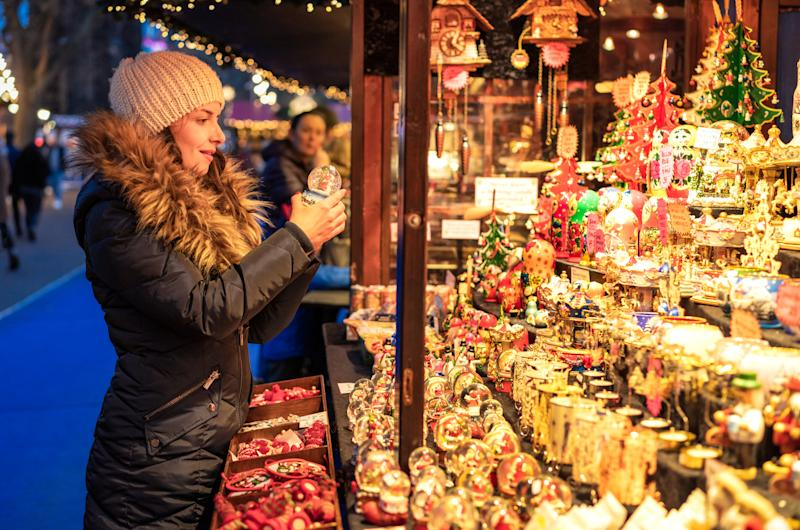 A woman looking at a snow-globe as she browses a stall of traditional Christmas decorations and toys at a market stall in Edinburgh, Scotland.