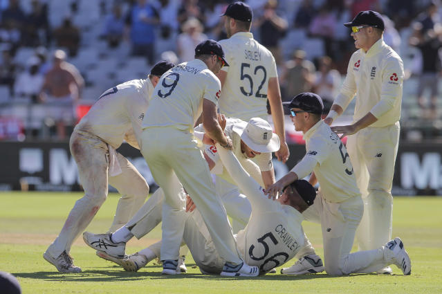 The England team celebrate the wicket of Anrich Nortje during day five of the second cricket test between South Africa and England at the Newlands Cricket Stadium in Cape Town, South Africa, Tuesday Jan. 7, 2020. (AP Photo/Halden Krog)