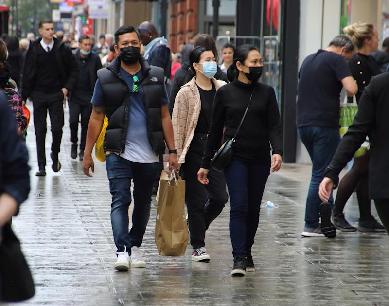 People walk along Oxford Street while while wearing face masks as a preventive measure against the spread of Coronavirus (COVID-19). Members of the public wearing protective face masks as they shop in Central London as further lockdown measures are proposed for the capital later this week. The UK government is preparing for a possible second nationwide lockdown to fight the spread of COVID-19. (Photo by Keith Mayhew / SOPA Images/Sipa USA)