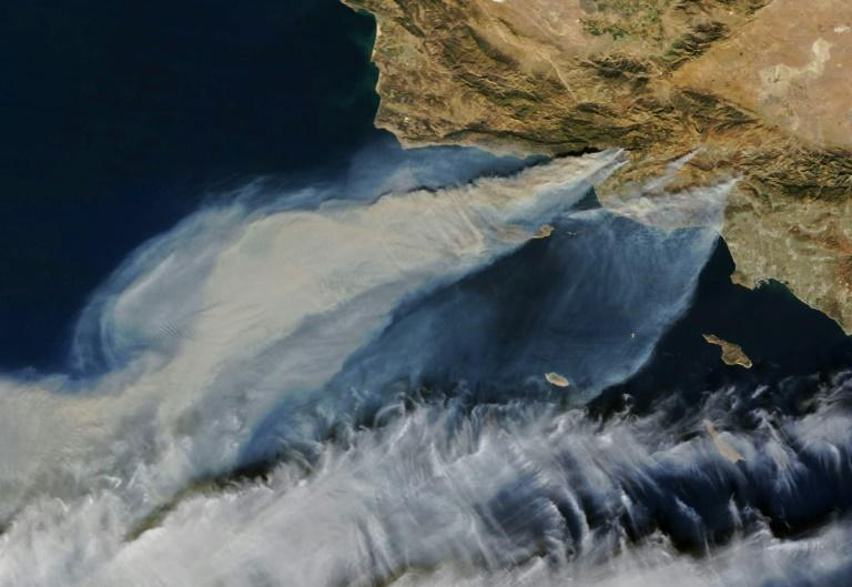 This image obtained from NASA Earth Observatory, shows smoke from the Thomas Fire (top C) in California blowing out to the Pacific Ocean on December 5, 2017, along with smoke from the Creek and Rye fires (top R)
