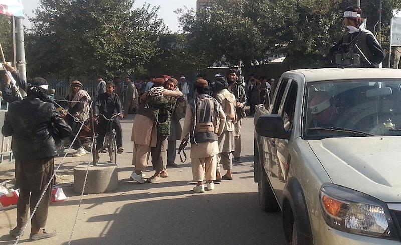 Taliban fighters hug each other a day after they overran the strategic northern city of Kunduz, on September 29, 2015 (AFP Photo/)