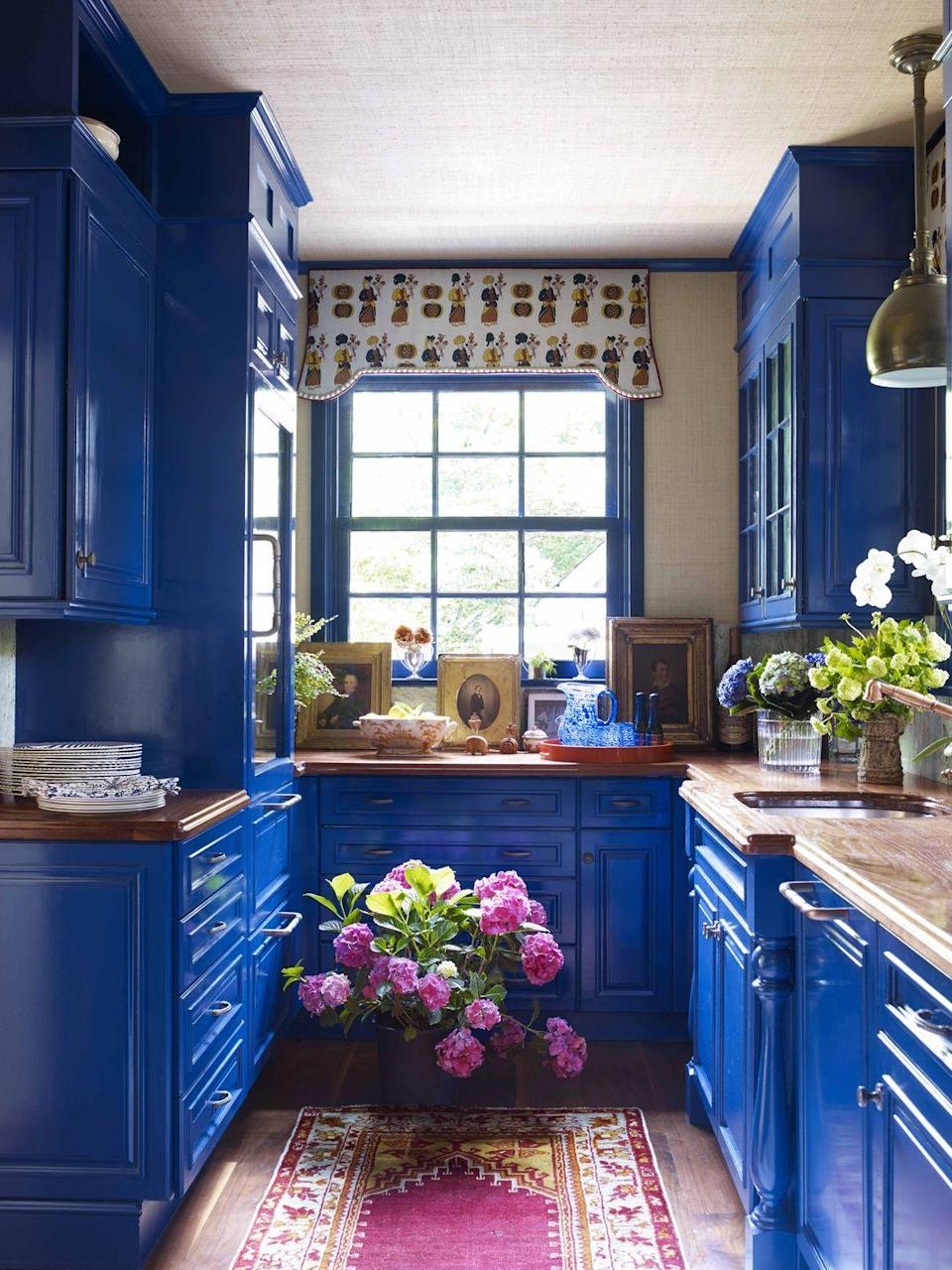 """<p>At this Newport, Rhode Island, home designed by <a href=""""https://www.ruthiesommers.com/"""" rel=""""nofollow noopener"""" target=""""_blank"""" data-ylk=""""slk:Ruthie Sommers"""" class=""""link rapid-noclick-resp"""">Ruthie Sommers</a>, the bar cabinetry is lacquered a custom color from <a href=""""https://www.finepaintsofeurope.com/"""" rel=""""nofollow noopener"""" target=""""_blank"""" data-ylk=""""slk:Fine Paints of Europe"""" class=""""link rapid-noclick-resp"""">Fine Paints of Europe</a>. The whimsical valence is covered a <a href=""""https://www.katieridder.com/products/fabrics.html"""" rel=""""nofollow noopener"""" target=""""_blank"""" data-ylk=""""slk:Katie Ridder fabric"""" class=""""link rapid-noclick-resp"""">Katie Ridder fabric</a>. The grasscloth wallcovering on the walls and ceiling is from <a href=""""https://www.astek.com/"""" rel=""""nofollow noopener"""" target=""""_blank"""" data-ylk=""""slk:Astek"""" class=""""link rapid-noclick-resp"""">Astek</a>; the rug is from <a href=""""https://lawrenceoflabrea.com/"""" rel=""""nofollow noopener"""" target=""""_blank"""" data-ylk=""""slk:Lawrence of La Brea"""" class=""""link rapid-noclick-resp"""">Lawrence of La Brea</a>. </p><p><a class=""""link rapid-noclick-resp"""" href=""""https://www.amazon.com/Kotobuki-Lacquer-Serving-Tray-2-Inch/dp/B00CJV9RTS?tag=syn-yahoo-20&ascsubtag=%5Bartid%7C10069.g.28837805%5Bsrc%7Cyahoo-us"""" rel=""""nofollow noopener"""" target=""""_blank"""" data-ylk=""""slk:Find A Similar Red Lacquer Tray Here"""">Find A Similar Red Lacquer Tray Here</a></p>"""