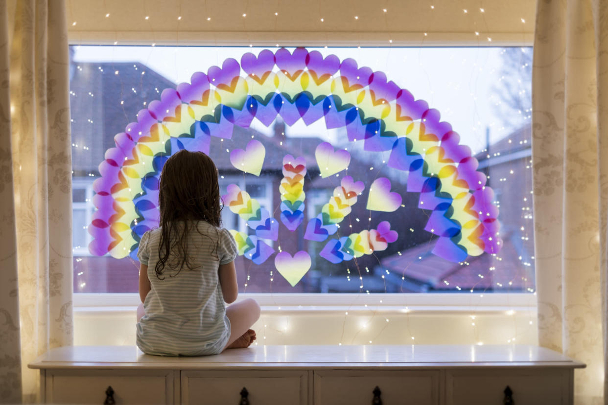 A little girl is looking out of a window at home.  She is sitting under a rainbow and fairy lights which have been displayed on the glass.  Stay at home social media campaign for coronavirus prevention.