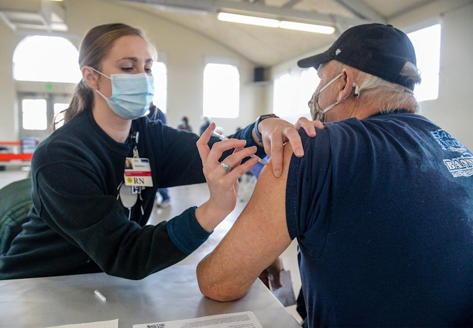 Benefis nurse Marissa Lencioni administers the Pfizer COVID-19 vaccine to Great Falls resident Mick Cabbage during a vaccination clinic Monday morning in the Family Living Center building at Montana ExpoPark.