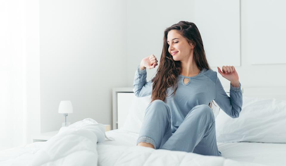 Beautiful woman waking up in her bed in the bedroom, she is stretching and smiling