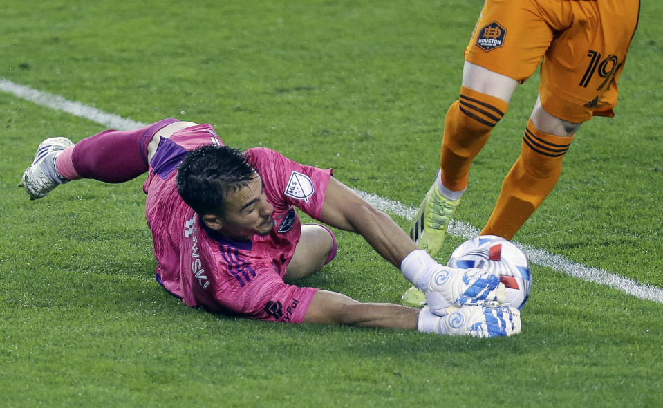 San Jose Earthquakes goalkeeper JT Marcinkowski (1) pushes the ball away from Houston Dynamo FC forward Tyler Pasher (19) during the first half of an MLS soccer game at BBVA Stadium on Friday, April 16, 2021, in Houston. (Godofredo A. Vásquez/Houston Chronicle via AP)