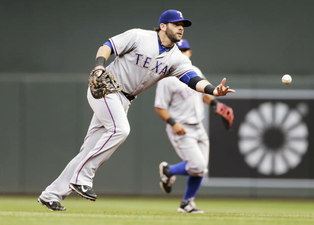Texas Rangers first baseman Mitch Moreland underhands the ball to pitcher Scott Baker at first for the out on a grounder by Minnesota Twins' Joe Mauer in the first inning of a baseball game Tuesday, May 27, 2014, in Minneapolis. (AP Photo/Jim Mone)