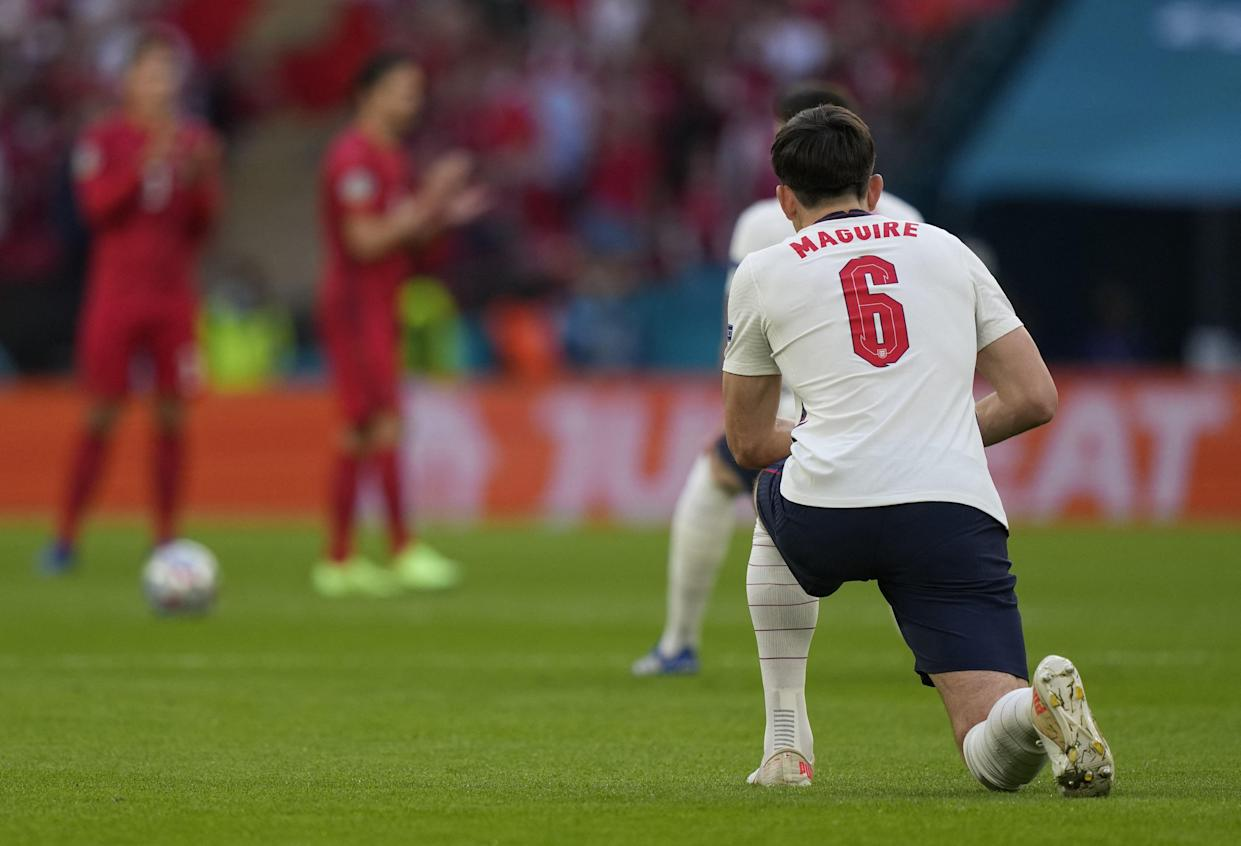 England's defender Harry Maguire takes a knee before the start of the UEFA EURO 2020 semi-final football match between England and Denmark at Wembley Stadium in London on July 7, 2021. (Photo by Frank Augstein / POOL / AFP) (Photo by FRANK AUGSTEIN/POOL/AFP via Getty Images)