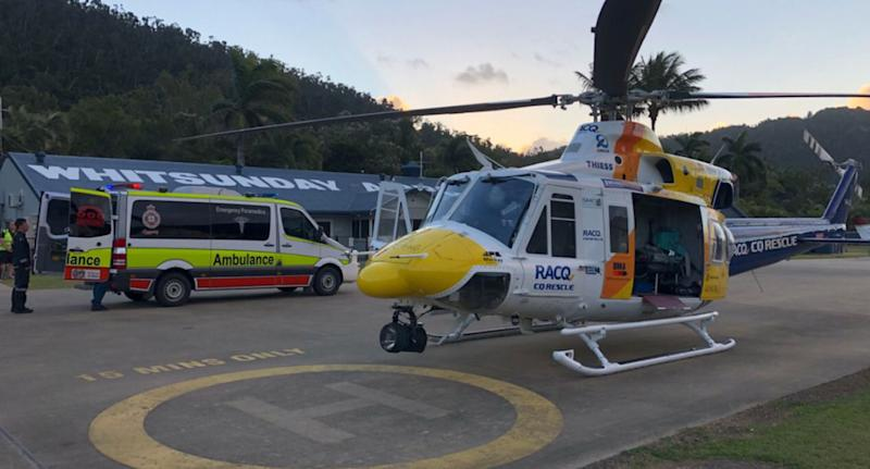 RACQ helicopter pictured at Whitsunday base in Queensland as man injured and pet dog killed by goanna.
