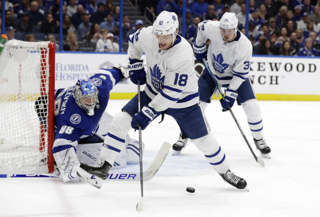 Toronto Maple Leafs left wing Andreas Johnsson (18) deflects a pass to center Auston Matthews (34) in front of Tampa Bay Lightning goaltender Andrei Vasilevskiy (88) during the first period of an NHL hockey game Thursday, Dec. 13, 2018, in Tampa, Fla. (AP Photo/Chris O'Meara)