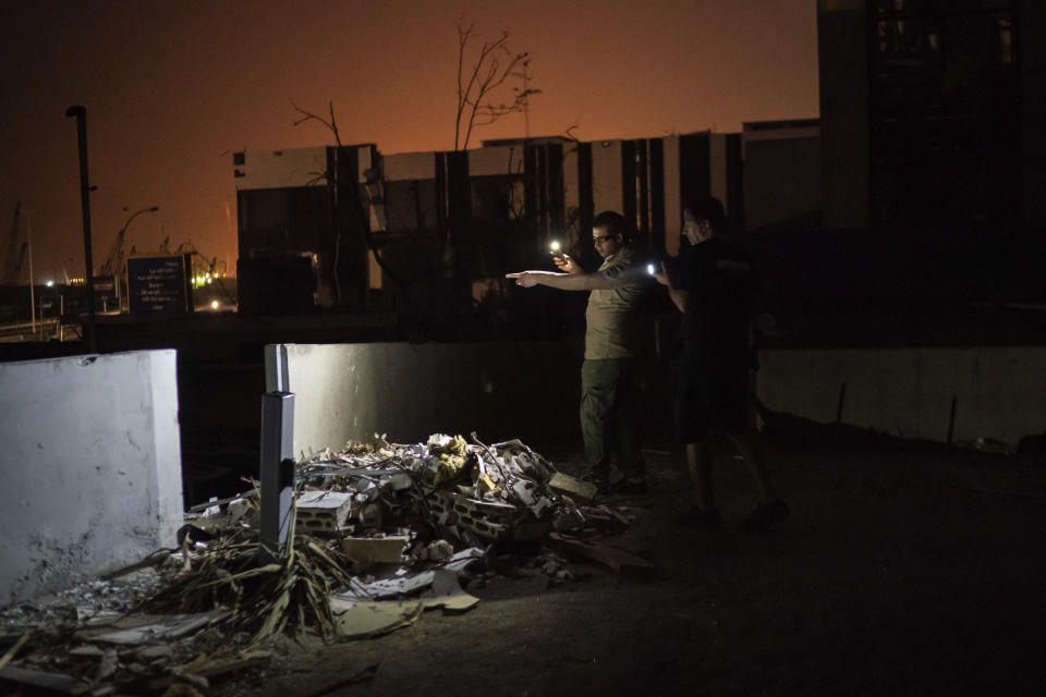 Kamal Khatib, of Animals Lebanon, and a security guard look for a family of cats hiding among debris of a damaged building near the site of last week's massive explosion in Beirut, Lebanon, Thursday, Aug. 13, 2020. Animals Lebanon deployed rescue teams around the city only hours after the blast and have since received hundreds of requests by pet owners asking to help track their dogs and cats among the chaos that unfolded after the blast. (AP Photo/Felipe Dana)