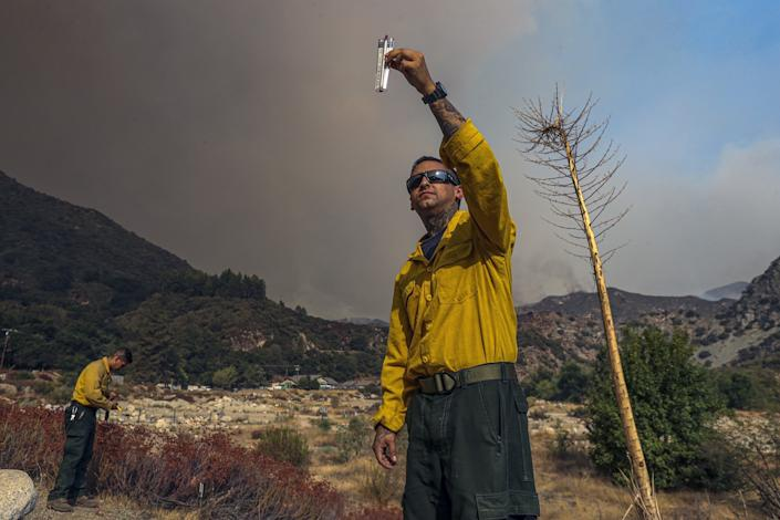 "Angeles National Forest firefighters Jessy Alvarez, left, and Gabriel Ayers take weather readings. <span class=""copyright"">(Irfan Khan / Los Angeles Times)</span>"