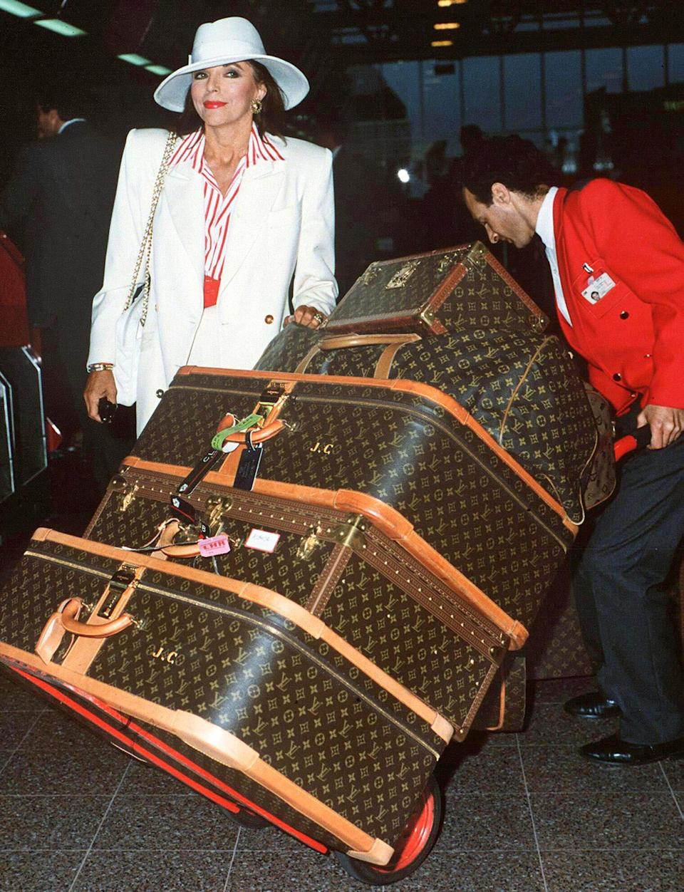 """<p>Famous for her love of luxury as Alexis Carrington Colby on the nighttime soap <em>Dynasty</em>, the star took logos to a new level at London's Heathrow. """"Carrying luggage can be a back-breaking job with me,"""" she tweeted in 2018.</p>"""