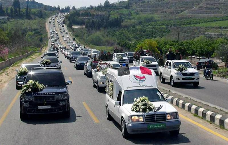 In this Monday, March 24, 2014 photo released by the Syrian official news agency SANA, a convoy carrying the coffin of the commander of the pro-government National Defense Forces Hilal Assad, during his funeral in Latakia province, Syria. State TV reported late Sunday that Hilal Assad was killed in the fighting against opposition fighters in Kassab. The commander was a member of Syrian President Bashar Assad's family but the TV did not say if they were close relatives. (AP Photo/SANA)