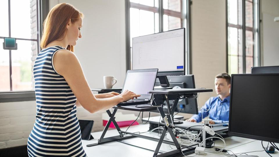 Business woman working on laptop computer at ergonomic standing desk.