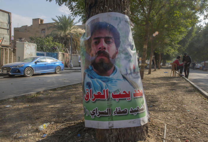 "A poster with a picture of an anti-government protester who was killed in demonstrations, and Arabic that reads, ""no one loves Iraq like he did, the Martyr Safa al-Sarai,"" hangs on a tree near Tahrir square, in Baghdad, Iraq, Wednesday, Dec. 25, 2019. (AP Photo/Nasser Nasser)"