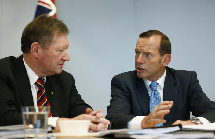 Australia's conservative leader and Prime Minister-elect Tony Abbott, right, meets the Secretary of the Department of the Prime Minister and Cabinet Ian Watt in Sydney, Sunday, Sept. 8, 2013. A new government prepared to take control of Australia on Sunday, with policies to cut pledges in foreign aid and to wind back greenhouse gas reduction measures in an effort to balance the nation's books. Abbott's conservative Liberal party-led coalition won a crushing victory at elections Saturday against the center-left Labor Party, which had ruled for six years. (AP Photo/Daniel Munoz, Pool)