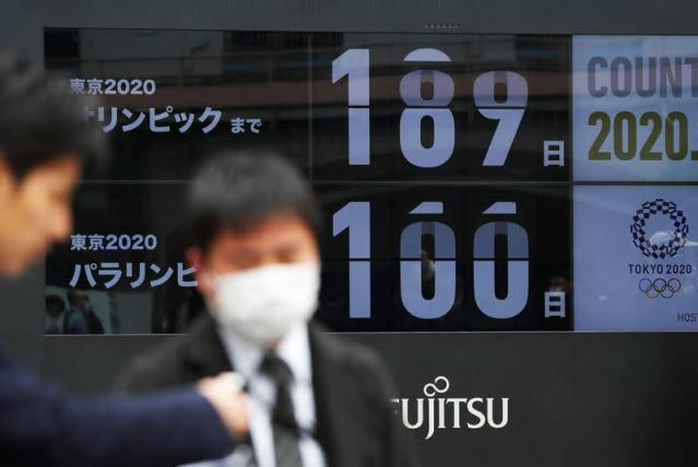 Passersby, wearing face masks due to the outbreak of the coronavirus disease (COVID-19), are reflected on shuffling screens counting down the days to the Tokyo 2020 Olympic Games and Tokyo 2020 Paralympic Games in Tokyo