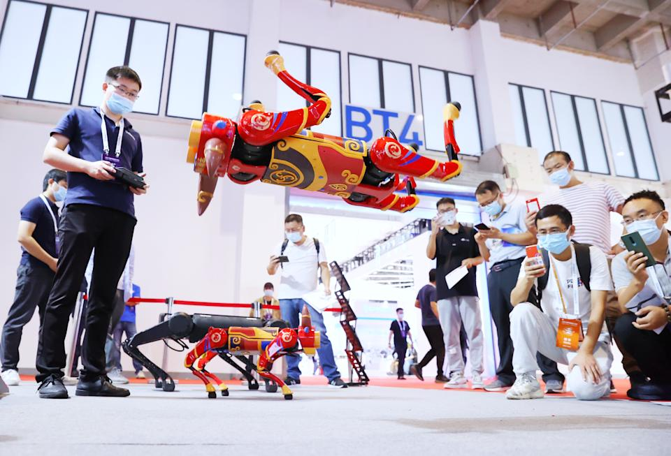 BEIJING, CHINA - SEPTEMBER 10: Visitors watch as a robot dog performs a backward somersault at the booth of Unitree Robotics during 2021 World Robot Conference (WRC) at Beijing Etrong International Exhibition & Convention Center on September 10, 2021 in Beijing, China. (Photo by Fu Ding/Beijing Youth Daily/VCG via Getty Images)