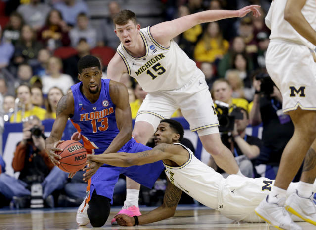 <p>Michigan's Charles Matthews, bottom, Jon Teske (15) and Florida's Kevarrius Hayes (13) scramble for the ball during the first half of a second round men's college basketball game in the NCAA Tournament, in Des Moines, Iowa, Saturday, March 23, 2019. (AP Photo/Nati Harnik) </p>