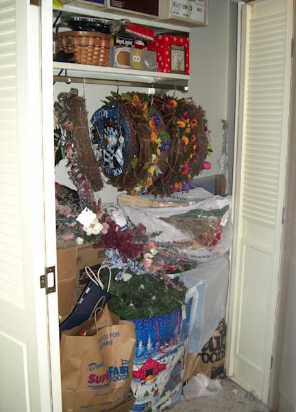 In this undated image released by Seriously Organized, a cluttered closet of Christmas decorations is shown prior to an organizing project. Nikki Havens of Seriously Organized in Bloomington, Minn., recommends starting with your entry hall closet. Small closet or walk-in, it's important to use the most convenient spot in your home to your advantage. (AP Photo/Seriously Organized)