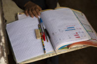 """Oscar Rojas, 11, readies his notebooks, pens and pencils, as he prepares for the arrival of his teacher Gerardo Ixcoy, in Santa Cruz del Quiche, Guatemala, Wednesday, July 15, 2020. """"I tried to get the kids their work sheets sending instructions via WhatsApp, but they didn't respond,"""" said the 27-year-old teacher. """"The parents told me that didn't have money to buy data packages (for their phones) and others couldn't help their children understand the instructions."""" (AP Photo/Moises Castillo)"""