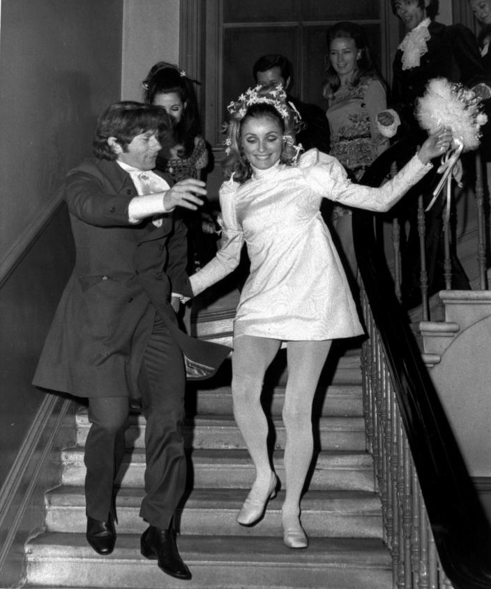 """FILE - In this Jan. 20, 1968 file photo, American actress Sharon Tate and Polish born film director Roman Polanski skip downstairs after their wedding at Chelsea Register Office in London. Tate was a model and rising film star after her breakout role in the 1966 film, """"Valley of the Dolls."""" She was 8-1/2 months pregnant when she was attacked as she pleaded with her Manson Family killers to spare the life of her unborn son as they killed five people at the home she and Polanski shared in the Bel-Air area of Los Angeles on Aug. 8-9, 1969. (AP Photo/Eddie Worth, File)"""