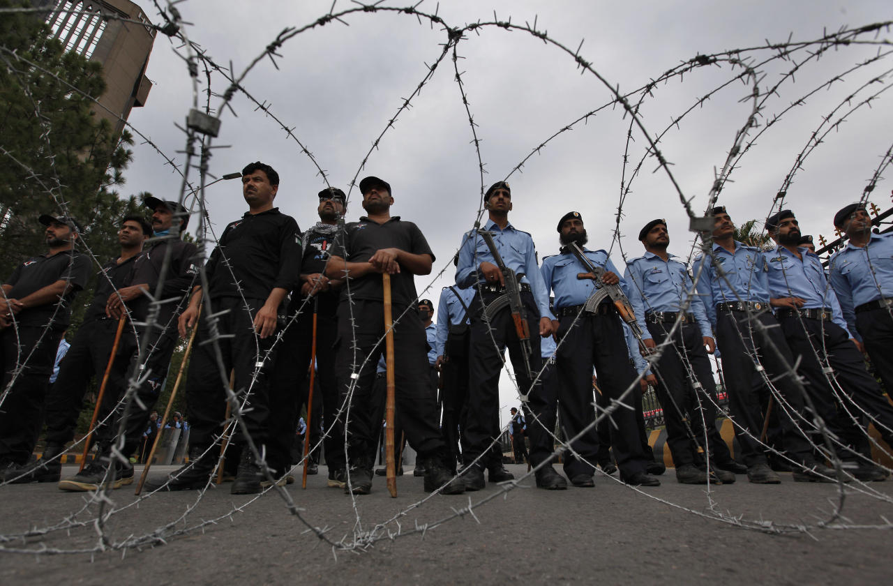 Pakistani police officers stand guard behind barbed wire to stop Shiite Muslims advancing toward the presidency, during a rally to condemn last weeks twin bombings in Parachinar, the center of Kurram region, in Islamabad, Pakistan, Wednesday, June 28, 2017. Battered by bombings that have killed scores of people, Pakistan's tribal Shiite Muslims took their protests to the Pakistani capital while in Pakistan's Kurram tribal region, where Shiites dominate. (AP Photo/Anjum Naveed)