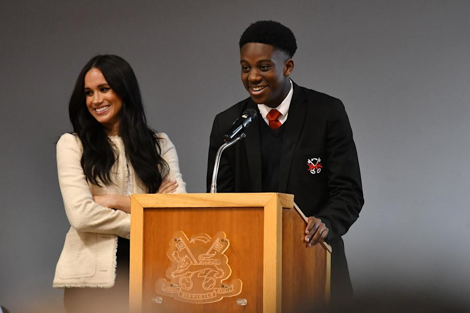LONDON, ENGLAND - MARCH 06: Meghan, Duchess of Sussex smiles as the student Aker Okoye speaks during a special school assembly at the Robert Clack Upper School in Dagenham ahead of International Women's Day (IWD) held on Sunday 8th March, on March 6, 2020 in London, England.   (Photo by Ben Stansall-WPA Pool/Getty Images)