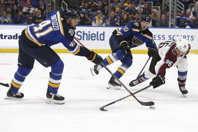 St. Louis Blues' Oskar Sundqvist (70), of Sweden, fends off Colorado Avalanche's Mikko Rantanen (96), of Finland, as teammate Robert Bortuzzo, left, clears the puck during the first period of an NHL hockey game Monday, Oct. 21, 2019, in St. Louis. (AP Photo/Scott Kane)
