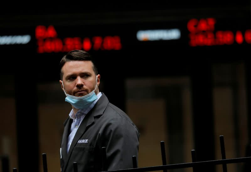 FILE PHOTO: FILE PHOTO: A trader walks past a digital stock price display outside the New York Stock Exchange in New York