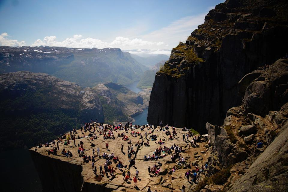 "According to NWF: Like many visitors to Norway, Mary Hall and her family felt drawn to make the arduous trek to Pulpit Rock, hiking for several hours to reach this remarkable table of stone nearly 2,000 feet above the winding waters of Lysefjord. ""I'm not afraid of heights,"" says Hall, who dangled her feet over the edge while absorbing the view. Hoping for a different perspective, her family hiked higher still, and Hall made this image from above. ""What I love about this shot,"" she says, ""is how all those people are having fun just enjoying the gorgeous scenery. The rock, the water, the clouds — it was just serene."" MARY HALL, 2020 National Wildlife® Photo Contest"