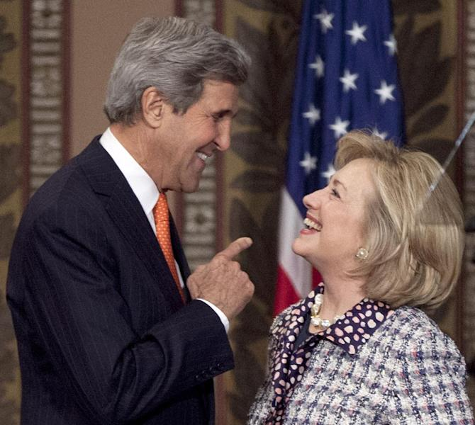 """Former Secretary of State Hillary Rodham Clinton and Secretary of State John Kerry greet each other on stage at Gaston Hall at Georgetown University in Washington, Friday, Nov. 15, 2013, during the """"Advance Afghan Women"""" symposium. Kerry and his predecessor, Clinton, said Afghanistan is reaching a turning point that will be critical to maintaining advances made by women since the end of Taliban rule. (AP Photo/Carolyn Kaster)"""