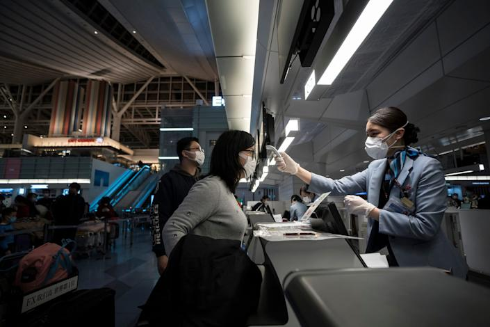 A passenger receives a temperature check before boarding a flight in Tokyo, Japan, on January 21, 2020.
