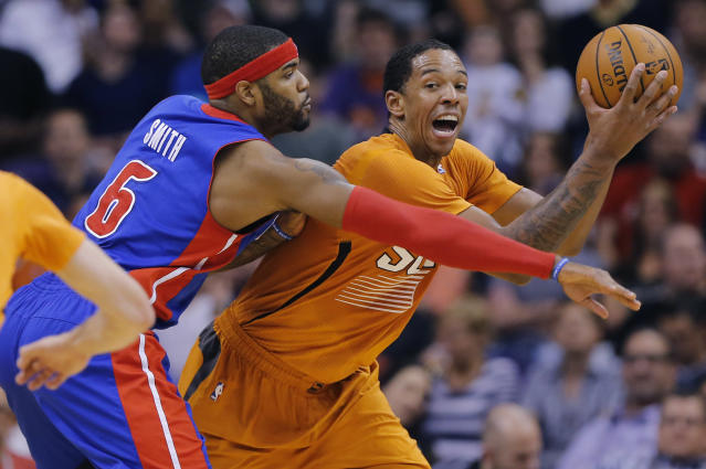 Detroit Pistons' Josh Smith (6) reaches in as Phoenix Suns' Channing Frye protects the ball during the first half of an NBA basketball game, Friday, March 21, 2014, in Phoenix. (AP Photo/Matt York)